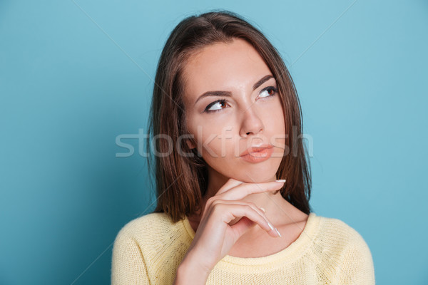 Stock photo: Close-up portrait of pensive girl thinking over blue background