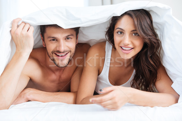 Happy couple lying in bed covered with blanket at home Stock photo © deandrobot