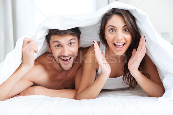 Szczęśliwy uśmiechnięty para bed pokryty koc Zdjęcia stock © deandrobot