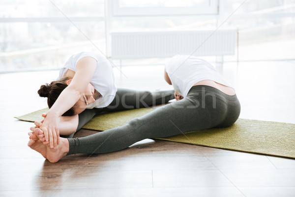 Two women stretching legs on green yoga mat Stock photo © deandrobot