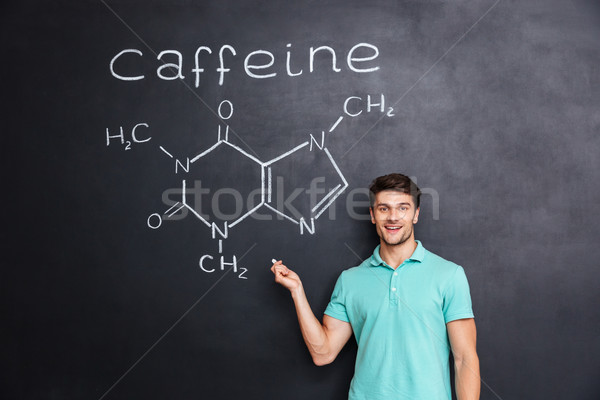 Smiling confident young student showing chemical structure of caffeine molecule Stock photo © deandrobot