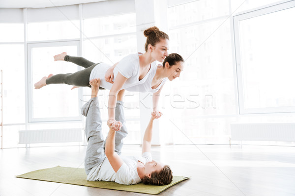 Group of two young women and man doing acro yoga Stock photo © deandrobot