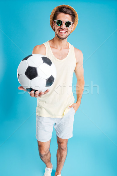 Cheerful young man giving you a football ball Stock photo © deandrobot