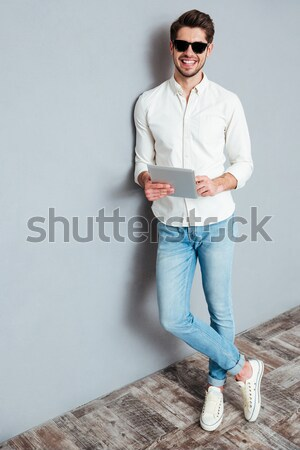 Stock photo: Smiling young man holding backpack and laptop