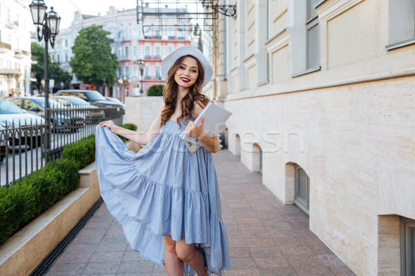 Happy woman in hat and blue dress in the city Stock photo © deandrobot
