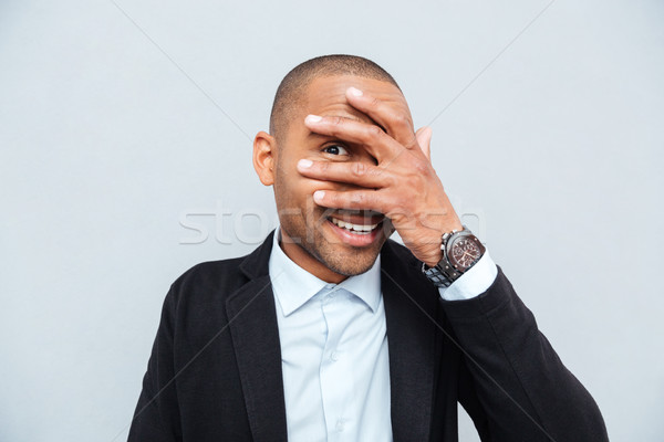 Young man hiding eyes behind his hand isolated over gray Stock photo © deandrobot
