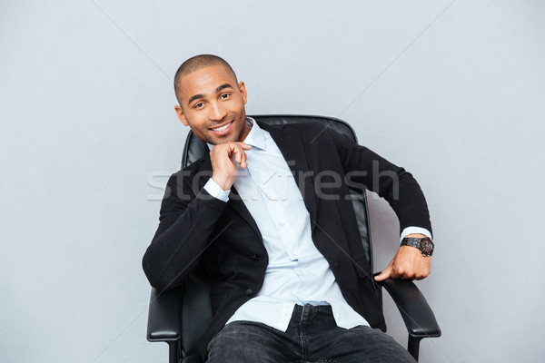 Confident smiling african american young man sitting in office chair Stock photo © deandrobot
