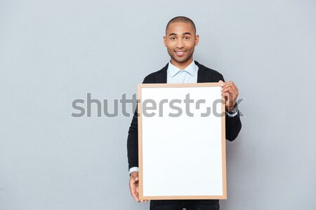 Stock photo: Smiling african american young man winking and holding whiteboard