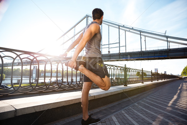 Side view of a sports man stretching with bridge railing Stock photo © deandrobot