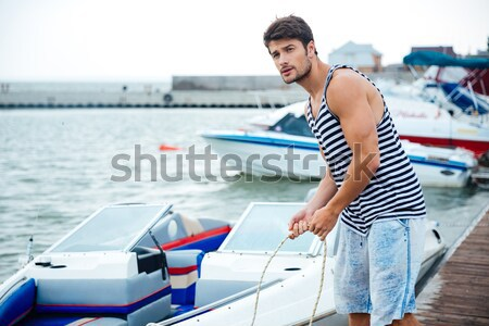 Handsome young sailor holding rope at the pier Stock photo © deandrobot
