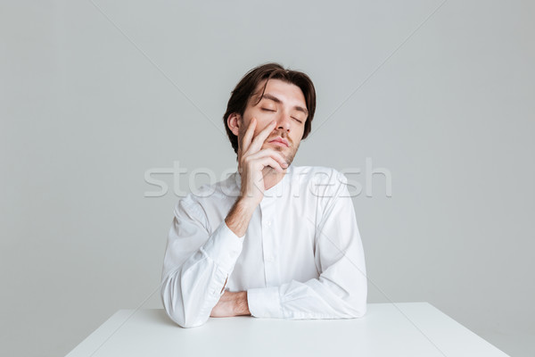 Man with eyes closed thinking about something at the table Stock photo © deandrobot