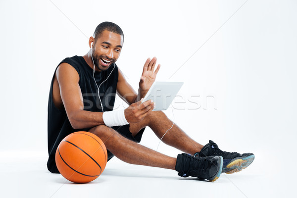 Stock photo: Man basketball player sitting and listening to music from tablet