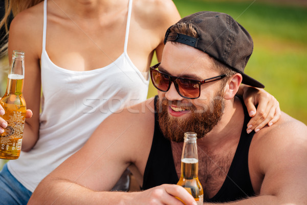 Smiling man sitting and drinking beer with his girlfriend outdoors Stock photo © deandrobot