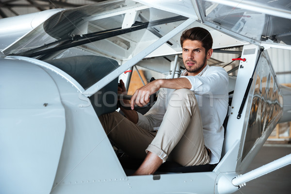 Attractive young man pilot in small aircraft Stock photo © deandrobot