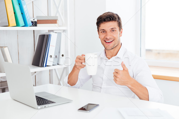Happy smiling businessman holding tea cup and showing thumbs up Stock photo © deandrobot