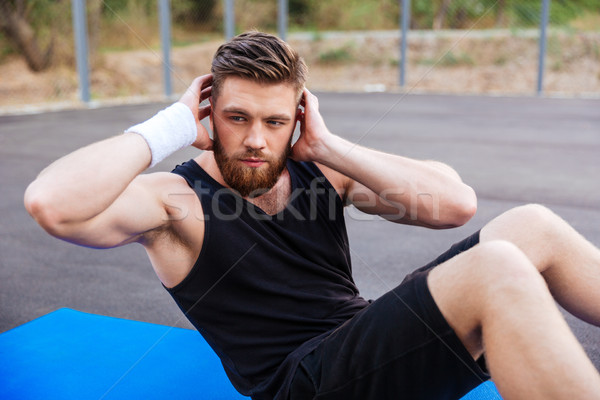 Man doing press exersices on the blue fitness mat outdoors Stock photo © deandrobot