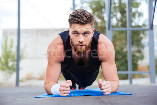 Sportsman doing plank exercise on blue fitness mat during workout Stock photo © deandrobot