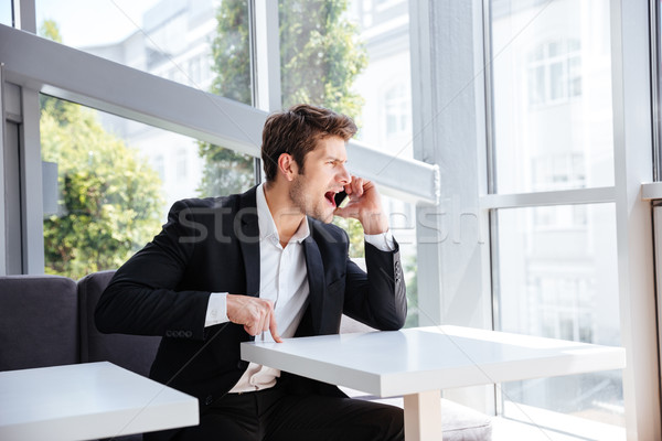 Mad angry young businessman sitting and shouting in cell phone Stock photo © deandrobot