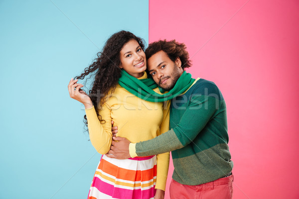 Smiling tender young couple in scarf standing and embracing Stock photo © deandrobot