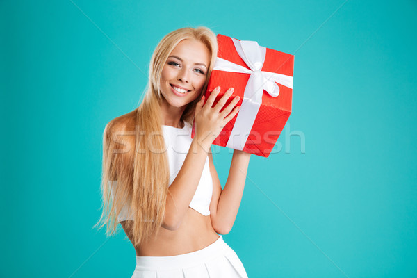 Portrait of a happy wondered woman holding gift box Stock photo © deandrobot