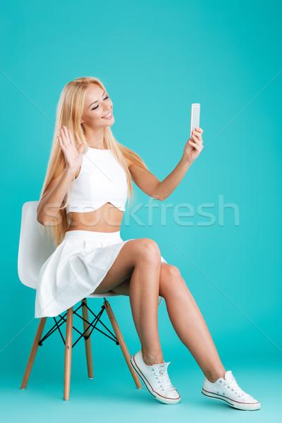 Boldog nő ül szék mobiltelefon integet Stock fotó © deandrobot