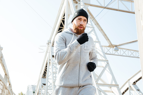 Close up portrait of a man jogger running across bridge Stock photo © deandrobot