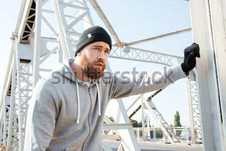 Athlete man in hoodie standing at the urban bridge Stock photo © deandrobot