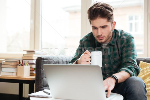 Man looking at laptop on sofa Stock photo © deandrobot