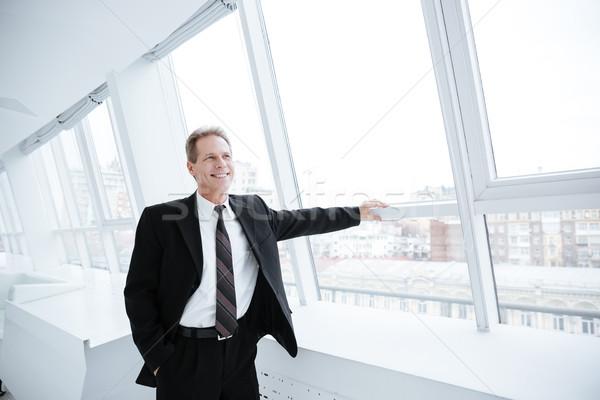 Smiling Elderly business man near the window Stock photo © deandrobot
