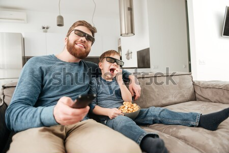Little boy watching TV with 3d glasses and holding popcorn Stock photo © deandrobot