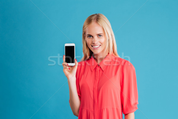 Portrait of a happy casual woman showing blank smartphone screen Stock photo © deandrobot