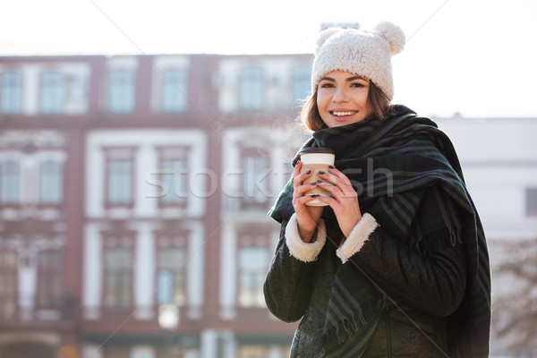 Smiling woman drinking coffee to go in the city Stock photo © deandrobot