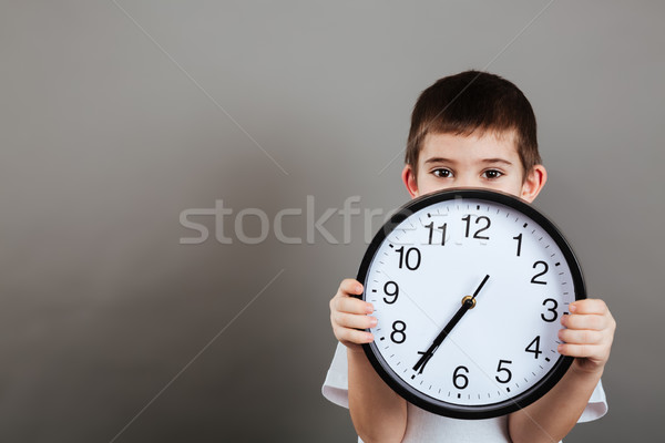 Cute little boy hiding his face behind the clock Stock photo © deandrobot