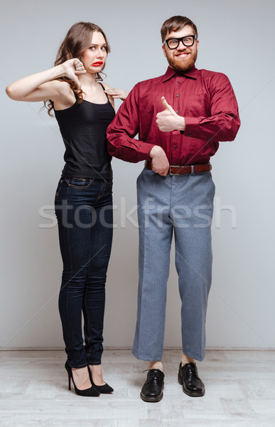 Vertical image Displeased Woman holding hand of Male nerd Stock photo © deandrobot