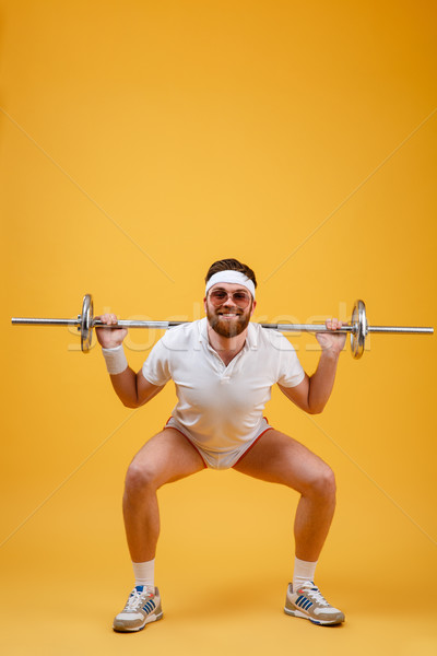 Happy young sportsman make sport exercises with barbell Stock photo © deandrobot