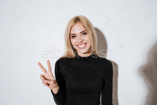 Smiling happy woman showing peace sign and looking at camera Stock photo © deandrobot
