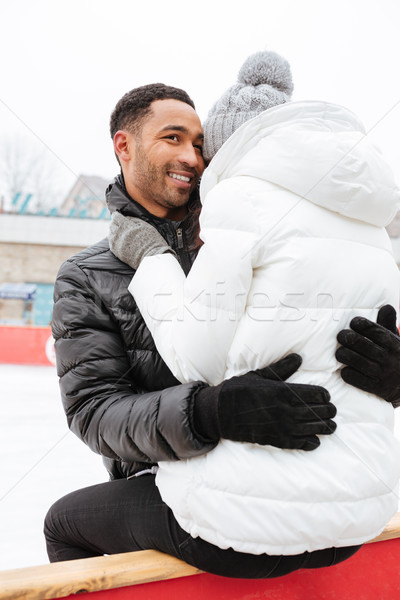 Attractive loving couple skating at ice rink outdoors and hugging. Stock photo © deandrobot