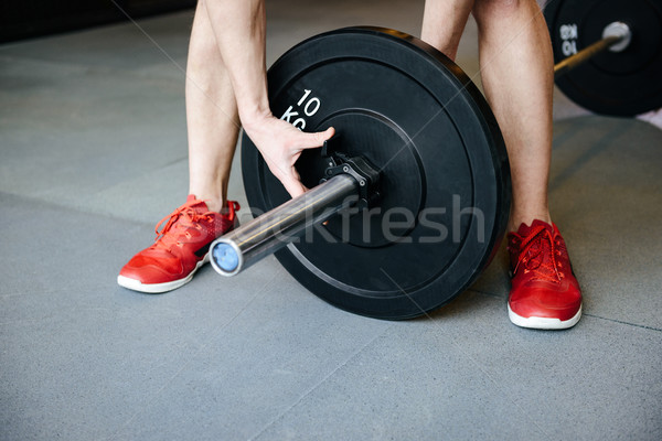 Cropped image of man collects the barbell Stock photo © deandrobot