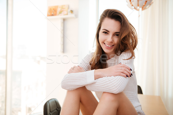 Portrait of a young woman in sweater sitting at home Stock photo © deandrobot