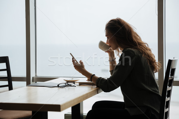 Woman using phone and drinking cofee Stock photo © deandrobot