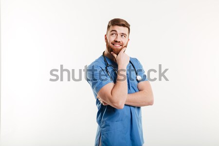 Smiling pensive male doctor looking away with hand on chin Stock photo © deandrobot