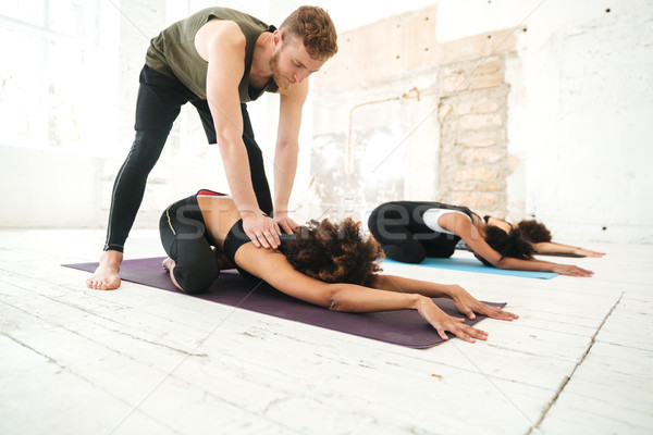 Male yoga instructor helping woman to stretch Stock photo © deandrobot