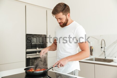 Happy bearded man with plate of vegetables on kitchen Stock photo © deandrobot
