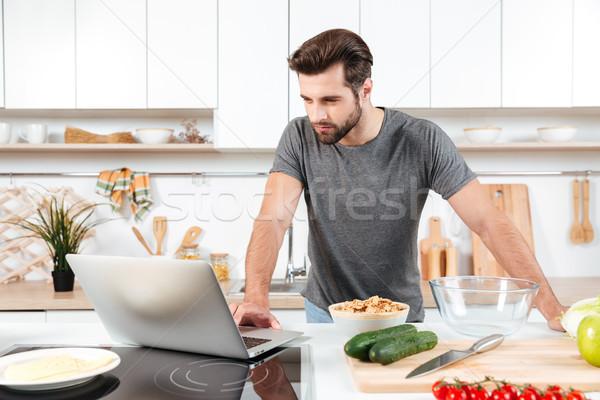 Homme regarder recette portable cuisine maison Photo stock © deandrobot