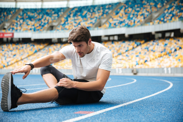 Young healthy sportsman stretching legs Stock photo © deandrobot