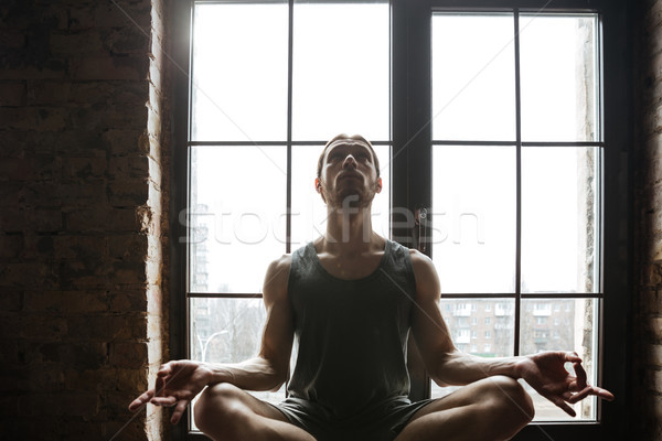 Portrait of a young sportsman meditating in lotus pose while sitting on the windowsill at the gym Stock photo © deandrobot