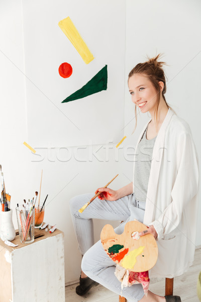 Happy young caucasian lady painter sitting at workspace Stock photo © deandrobot