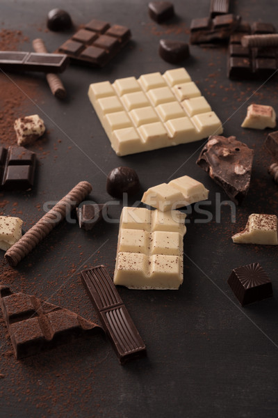 Big variety of chocolate bars crashed into pieces Stock photo © deandrobot