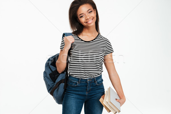 Cheerful african student girl wearing backpack and holding books Stock photo © deandrobot