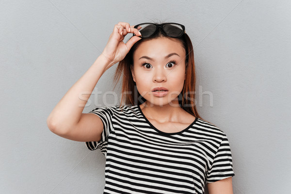 Surprised woman taking off her glasses Stock photo © deandrobot